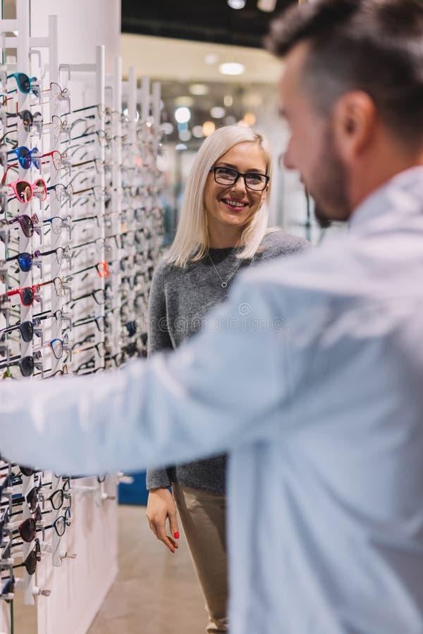 Mujer y óptico que eligen los vidrios imagenes de archivo