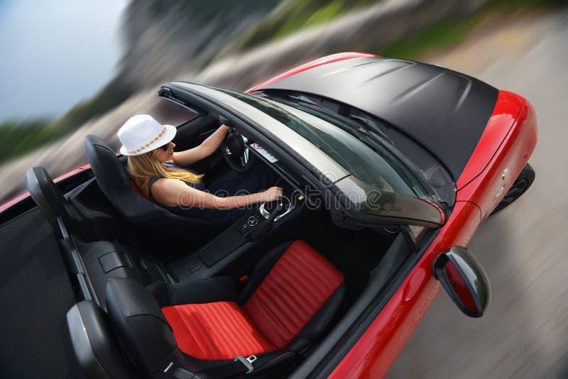 Mujer y cabriolé rojo fotografía de archivo