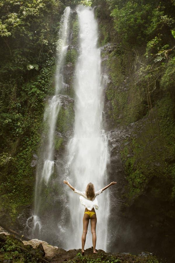 Mujer y cascada hermosas imagenes de archivo