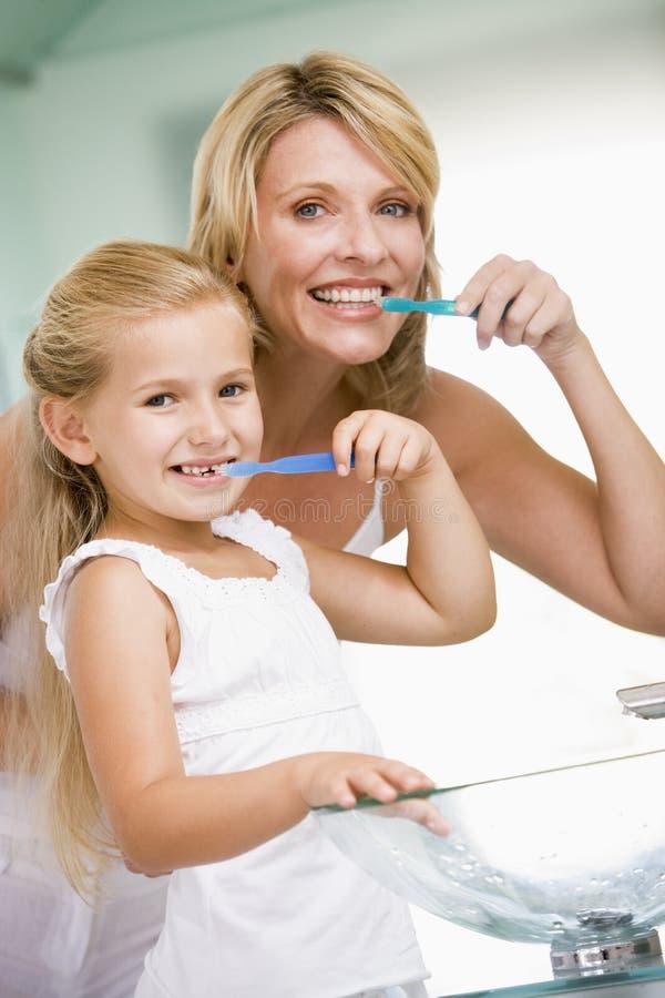 Mujer y chica joven en dientes que aplican con brocha del cuarto de baño imagenes de archivo
