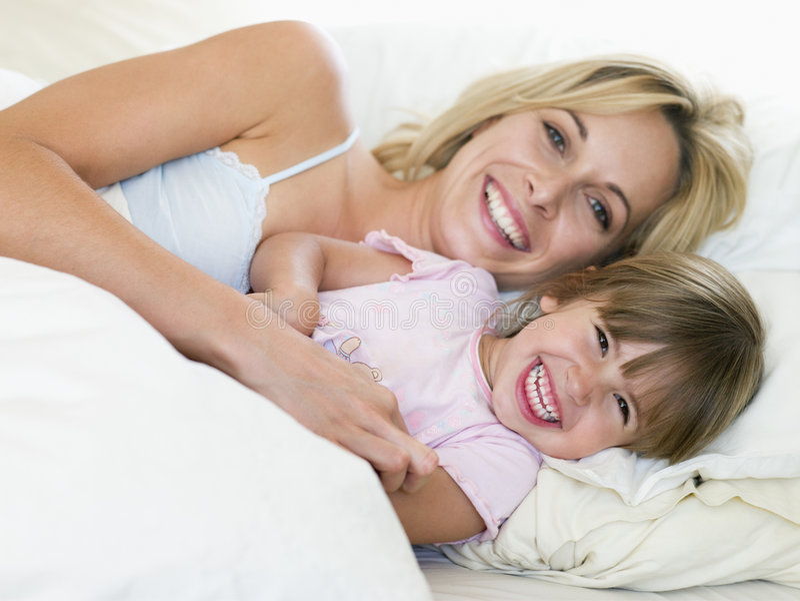 Mujer y chica joven en la sonrisa de la cama fotografía de archivo libre de regalías