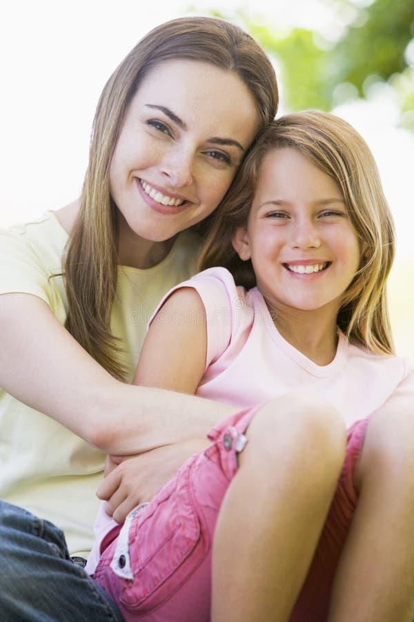 Mujer y chica joven que abrazan y que sonríen imágenes de archivo libres de regalías