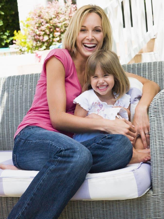 Mujer y chica joven que se sientan en la risa del patio fotografía de archivo
