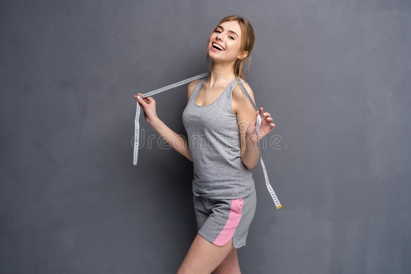 Mujer y cinta m?trica Muchacha joven, deportiva, apta y hermosa con la cinta m?trica fotos de archivo