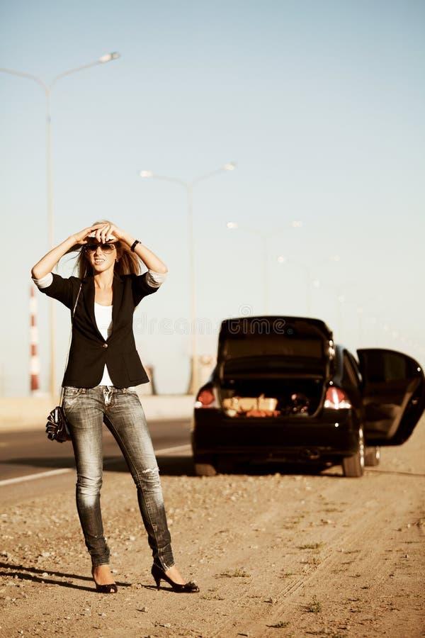 Mujer y coche quebrado. imagenes de archivo