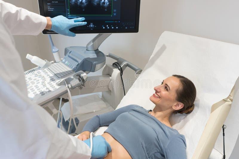 Mujer y doctor que miran la pantalla ultrasónica durante el examen fotografía de archivo libre de regalías