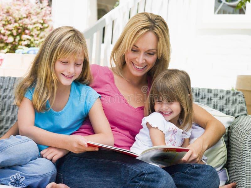 Mujer y dos chicas jóvenes que se sientan en la lectura del patio fotos de archivo