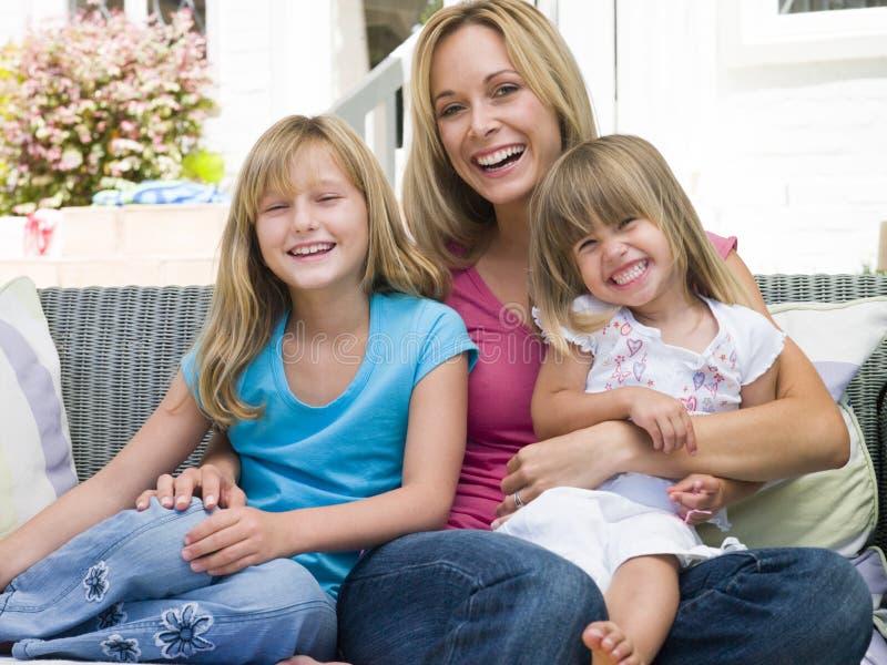 Mujer y dos chicas jóvenes que se sientan en la sonrisa del patio fotografía de archivo libre de regalías