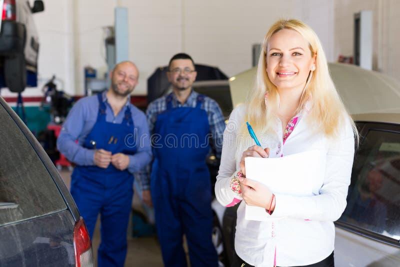 Mujer y dos mecánicos de automóviles foto de archivo libre de regalías