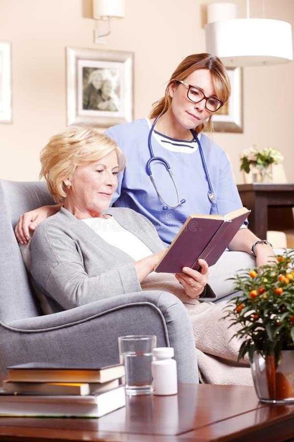 Mujer y enfermera mayores imagenes de archivo