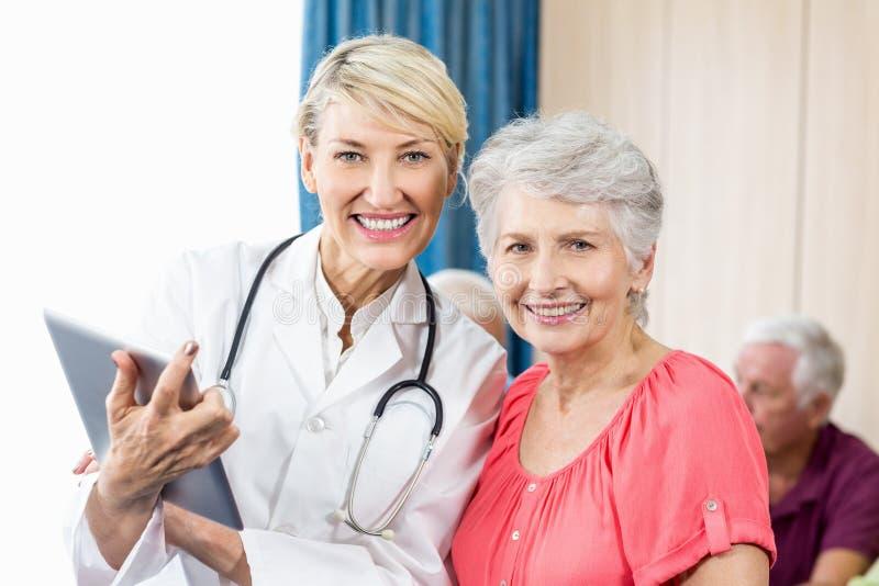 Mujer y enfermera mayores sonrientes que sostienen una tableta fotos de archivo