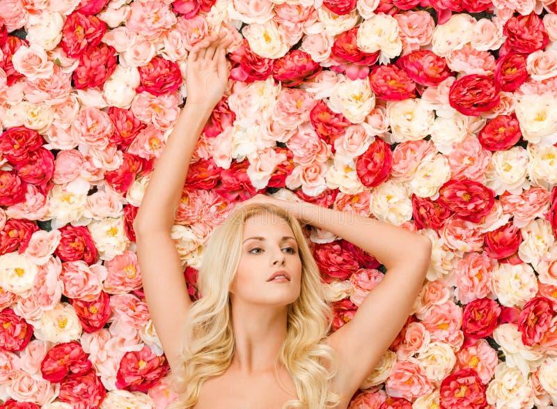Mujer y fondo por completo de rosas fotos de archivo