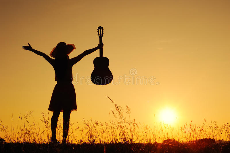 Mujer y guitarra felices con la silueta de la puesta del sol foto de archivo