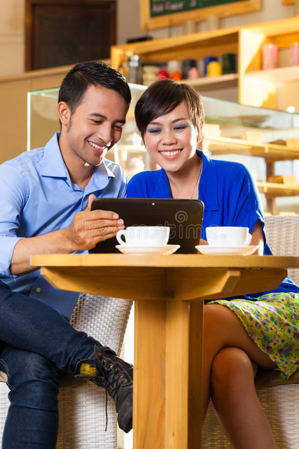 Mujer y hombre asiáticos en una cafetería foto de archivo