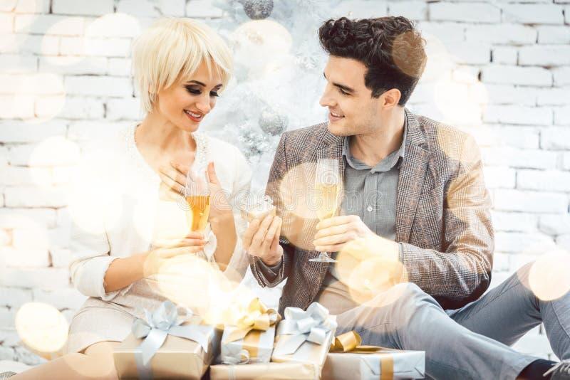 Mujer y hombre con el vino y presentes delante del árbol de navidad blanco foto de archivo