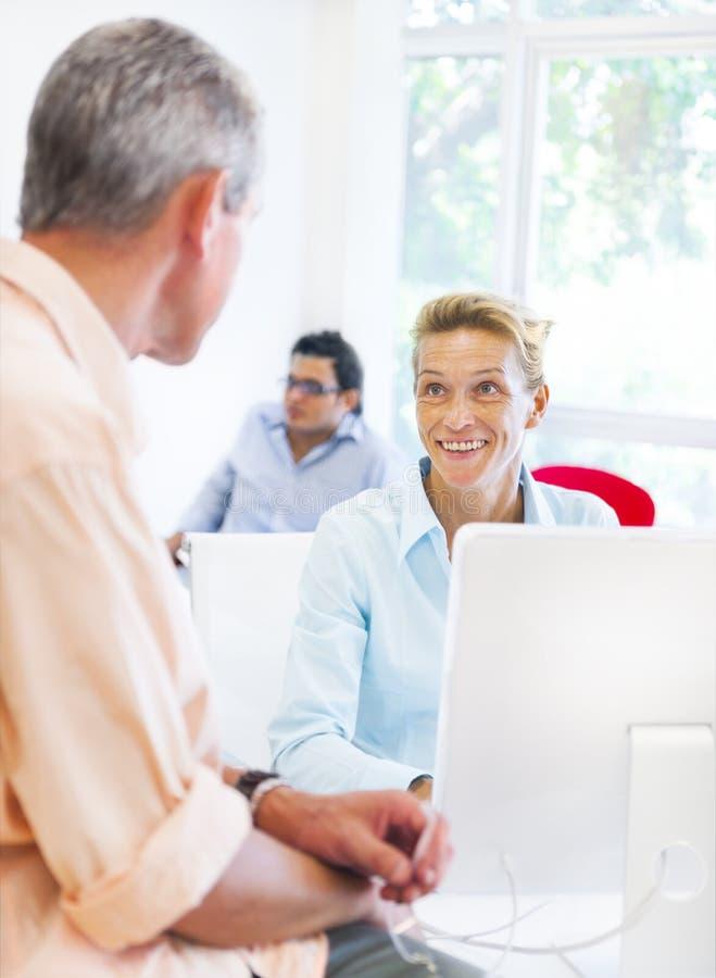 Mujer y hombre de negocios que hablan el uno al otro imagenes de archivo