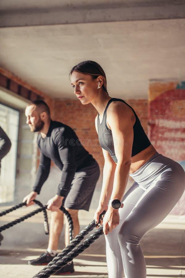 Mujer y hombre en el entrenamiento funcional del gimnasio con el ejercicio de la cuerda de la batalla imagenes de archivo
