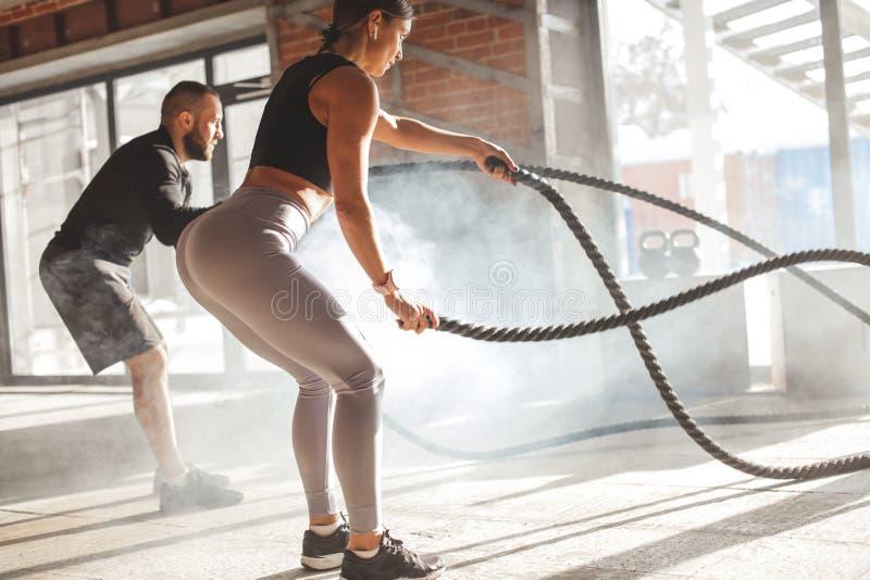 Mujer y hombre en el entrenamiento funcional del gimnasio con el ejercicio de la cuerda de la batalla imagen de archivo