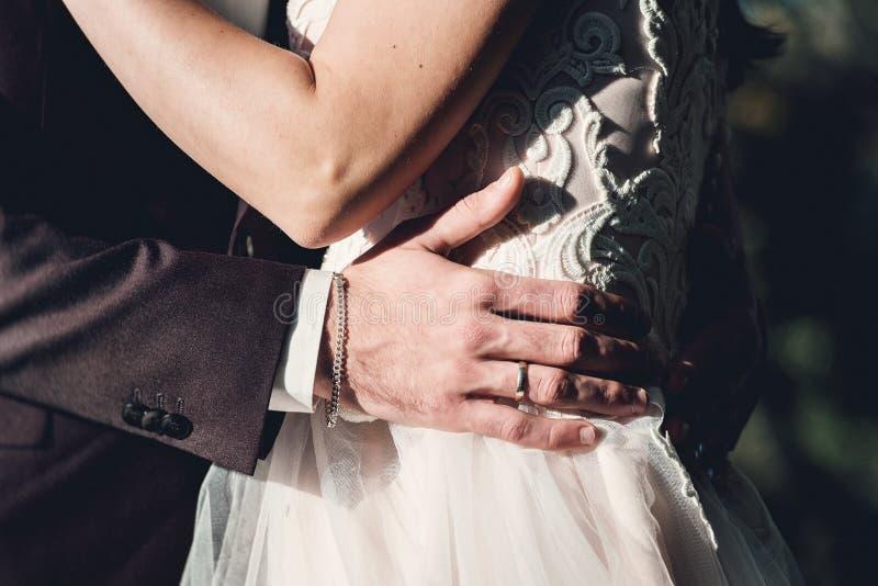 Mujer y hombre en el vestido de boda al aire libre huging Un hombre joven abraza suavemente a su novia en un vestido de boda imagen de archivo libre de regalías
