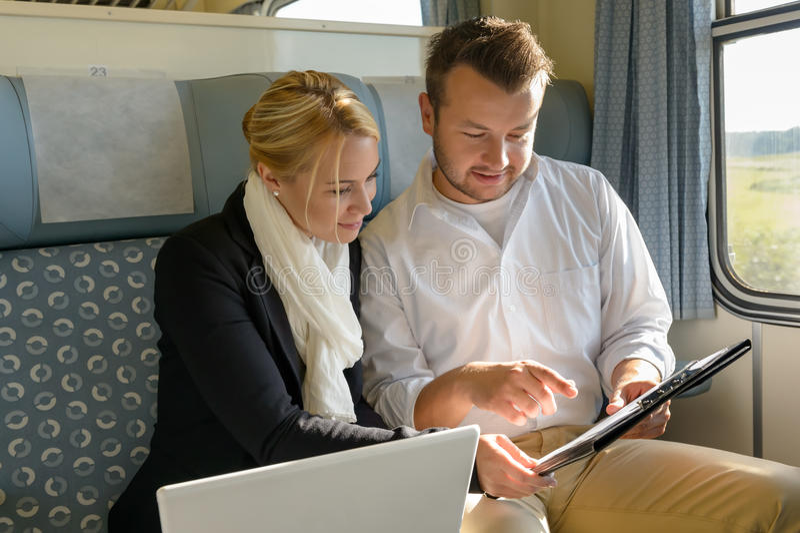 Mujer y hombre en tablero de la computadora portátil del tren imagen de archivo libre de regalías