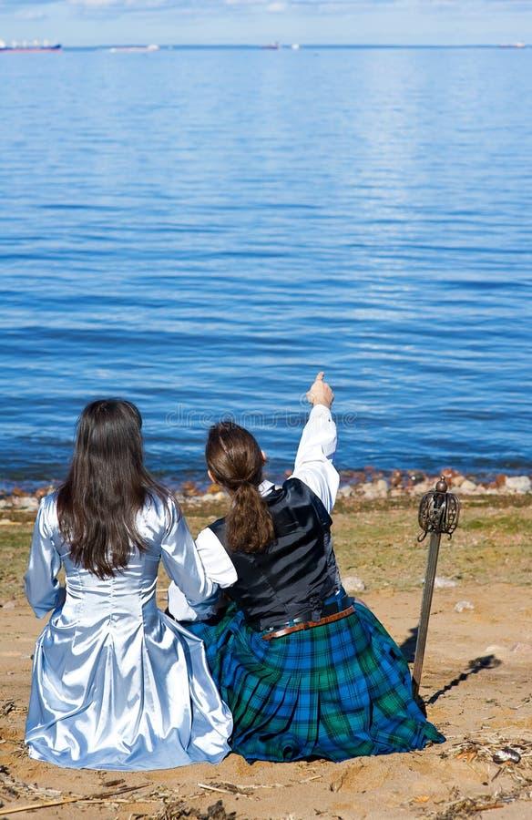 Mujer y hombre en traje escocés cerca del mar imagen de archivo libre de regalías