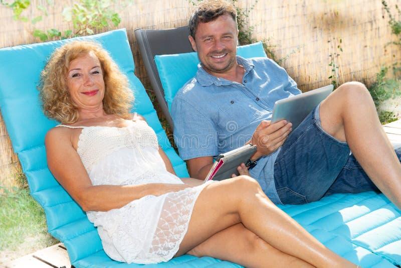 Mujer y hombre mayor con el hogar al aire libre de la tableta del ordenador en día de verano fotos de archivo