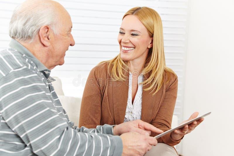 Mujer y hombre mayor que usa la tableta foto de archivo
