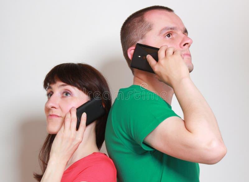 Mujer y hombre que hablan en el teléfono móvil imagen de archivo libre de regalías