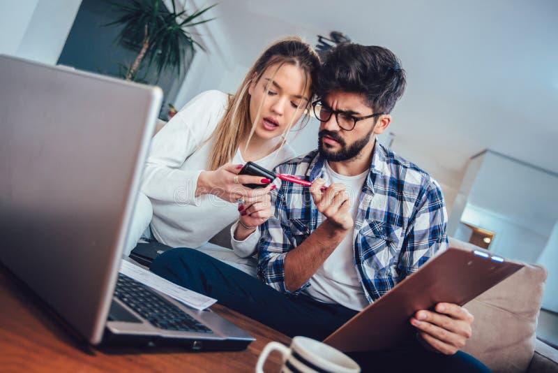 Mujer y hombre que hacen el papeleo junto, pagando impuestos en línea foto de archivo libre de regalías