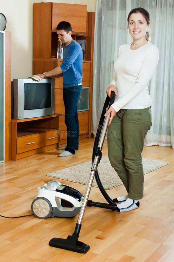 Mujer y hombre que hacen el quehacer doméstico junto en hogar imagen de archivo