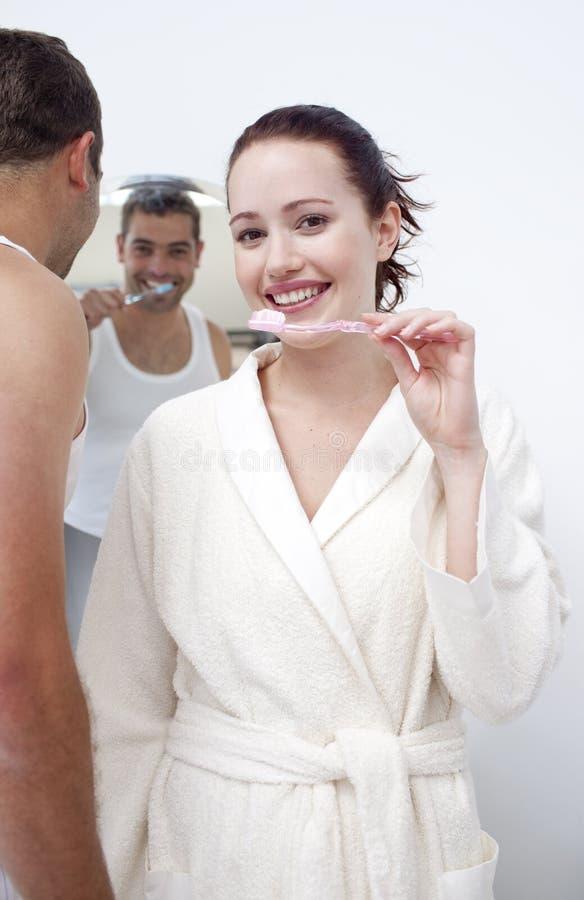 Mujer y hombre que limpian sus dientes en cuarto de baño fotografía de archivo