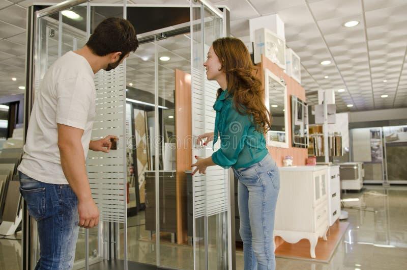 Mujer y hombre que miran recintos de la ducha fotos de archivo libres de regalías