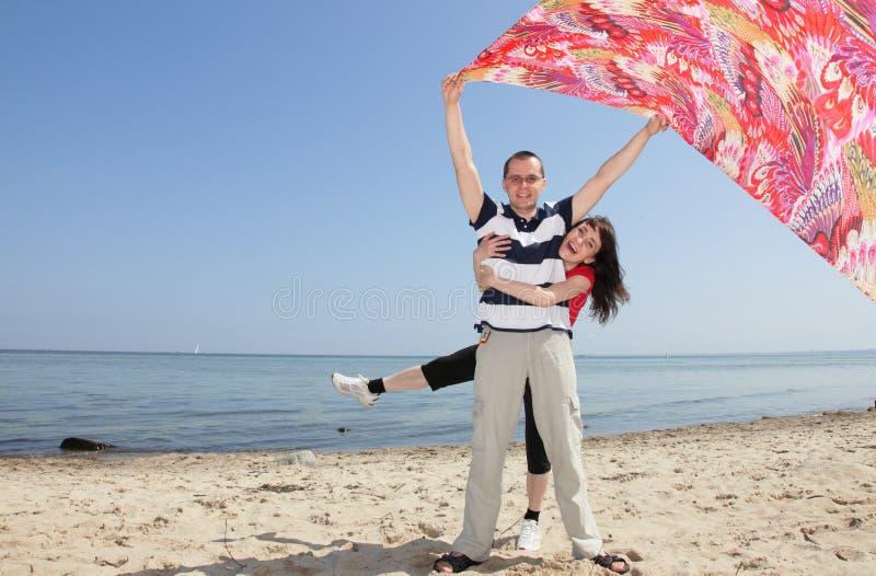 Mujer y hombre que presentan con la tela roja foto de archivo
