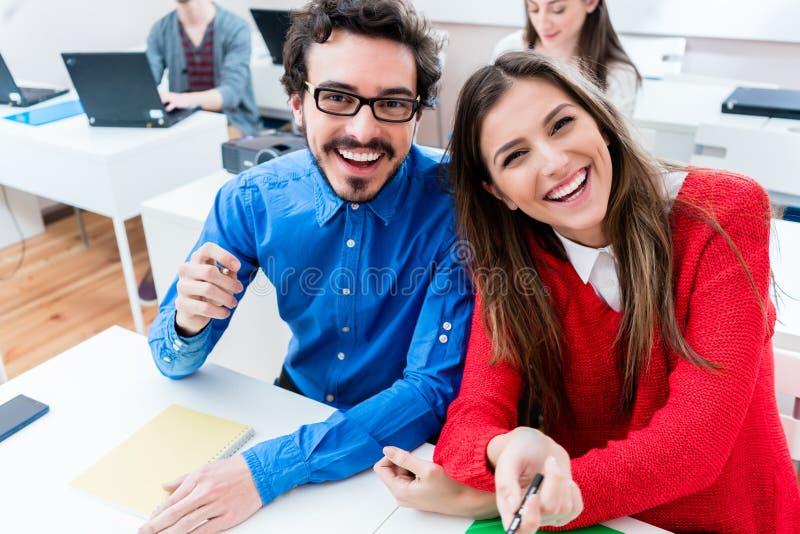 Mujer y hombre que se divierten como estudiantes en la universidad imágenes de archivo libres de regalías