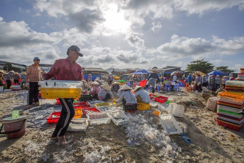 Mujer y hombre que trabajan en la playa cerca de mercado de pescados largo de Hai imagenes de archivo