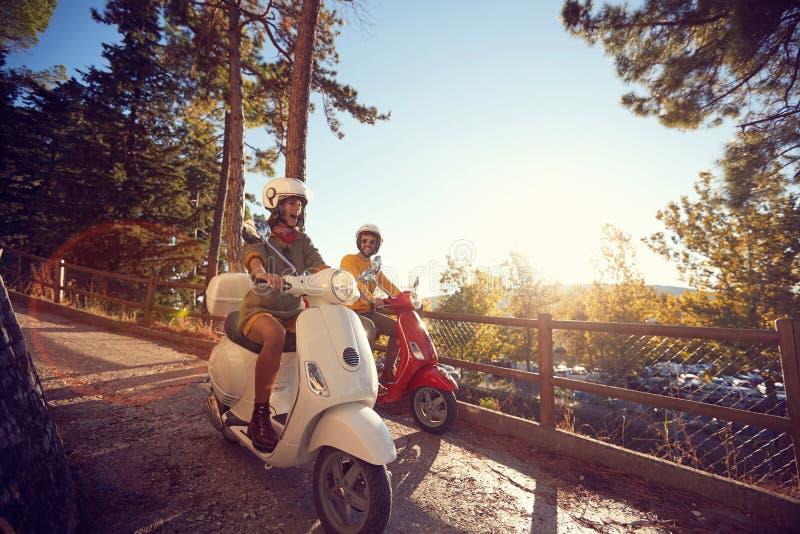 Mujer y hombre que viajan en la vespa y que se divierten de vacaciones foto de archivo
