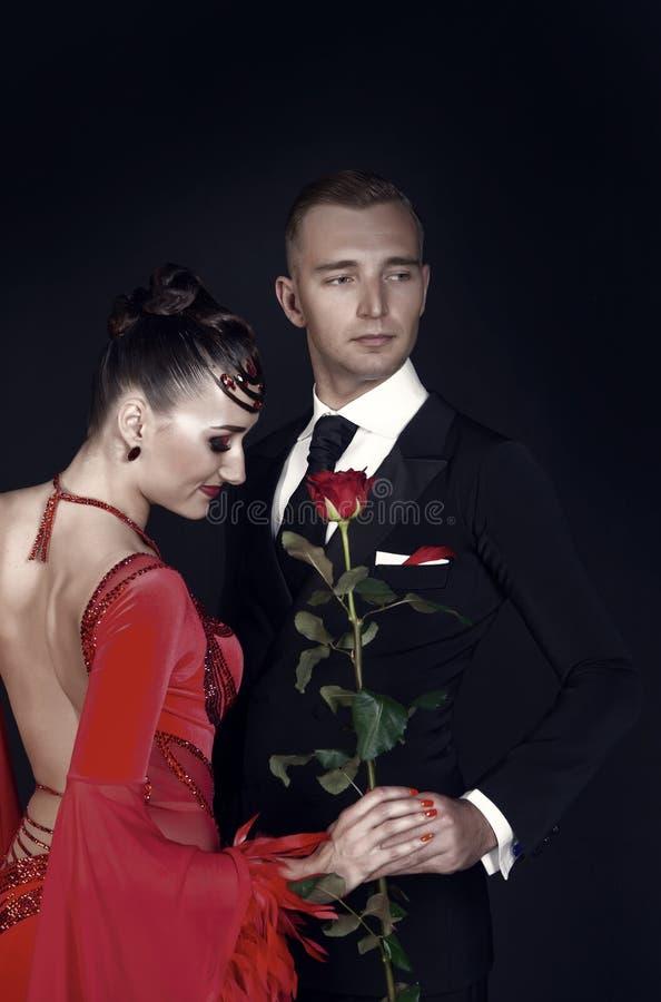 Mujer y hombre sensuales con la flor color de rosa Mujer en vestido y machista rojos en smoking Pares de los bailarines del salón fotografía de archivo libre de regalías