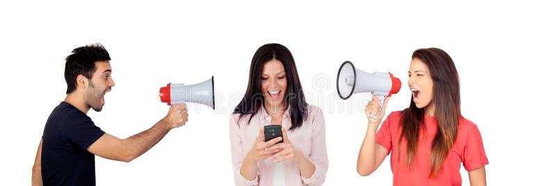 Mujer y hombres con un megáfono que gritan un amigo con un móvil imagenes de archivo