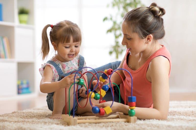 Mujer y juego de niños en cuarto de niños imagenes de archivo