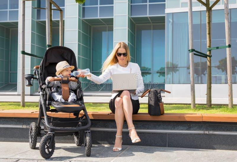 Mujer y madre de negocios que trabajan en el ordenador portátil con el bebé en cochecito foto de archivo libre de regalías