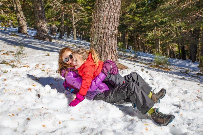 Mujer y muchacha que abrazan la mentira en la nieve foto de archivo