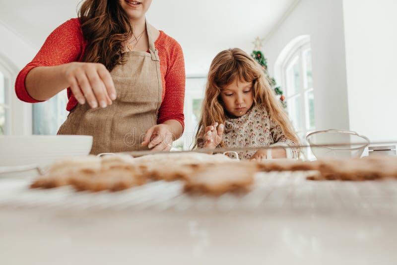 Mujer y muchacha que hacen las galletas de la Navidad imagen de archivo libre de regalías
