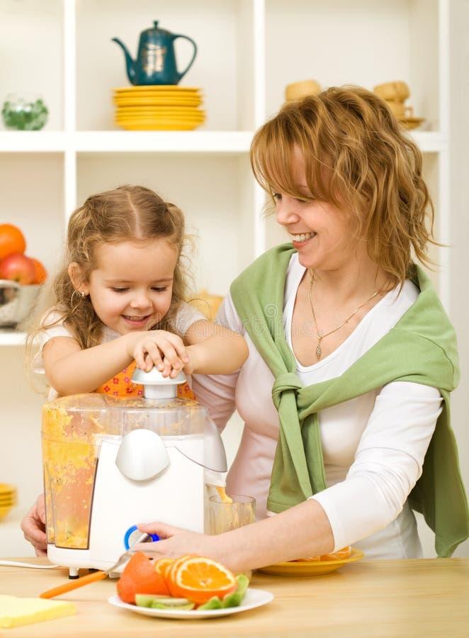 Mujer y niña que hacen el zumo de fruta fotografía de archivo