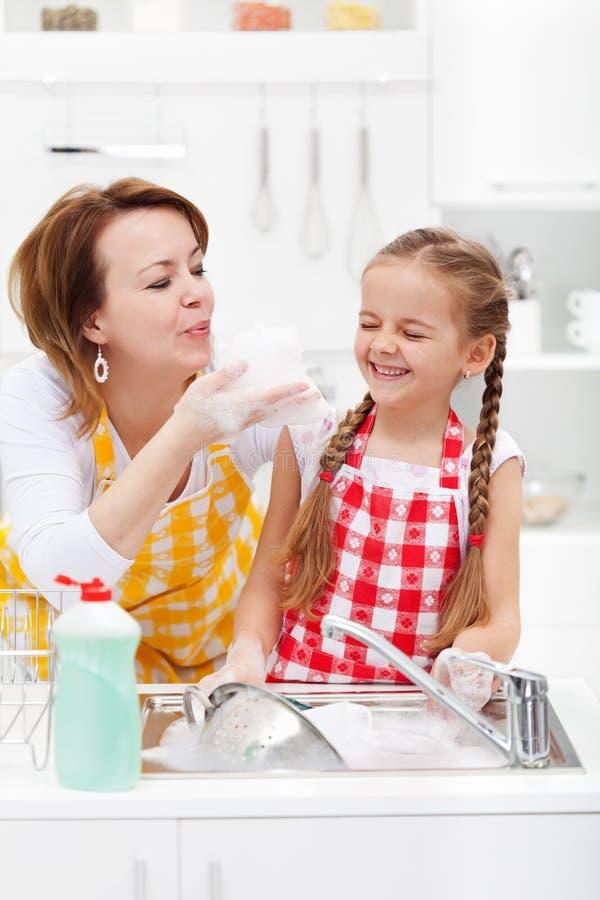 Mujer y niña que se divierten que lava los platos imágenes de archivo libres de regalías