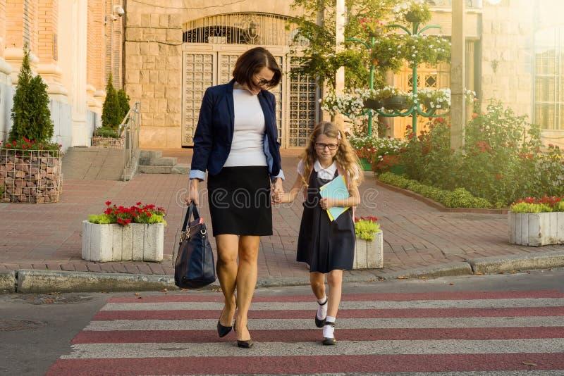 Mujer y niño - colegiala joven que lleva a cabo las manos, en el cr de la cebra fotografía de archivo libre de regalías