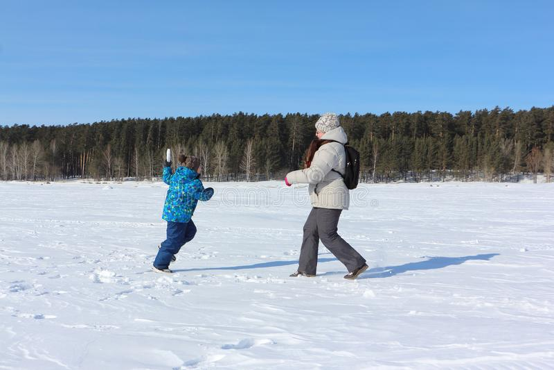 Mujer y niño pequeño que juegan bolas de nieve imagen de archivo libre de regalías