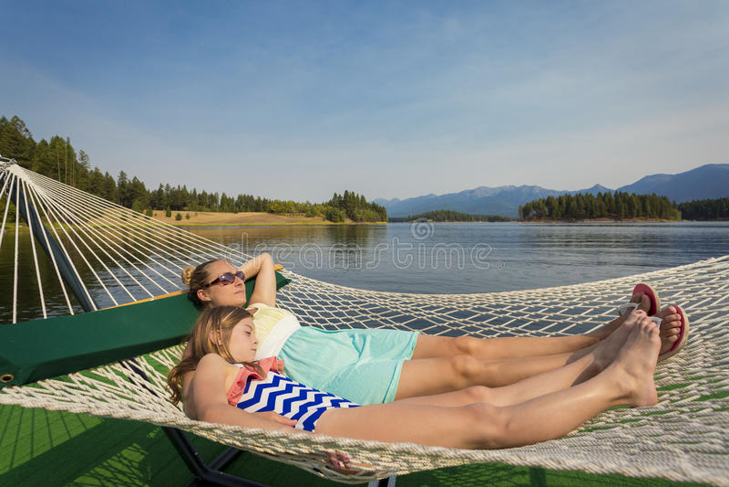 Mujer y niño que se relajan en una hamaca en un lago hermoso mountain imágenes de archivo libres de regalías