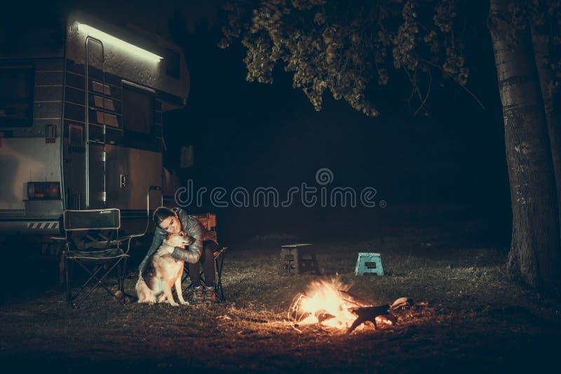 Mujer y perro cerca de la hoguera foto de archivo