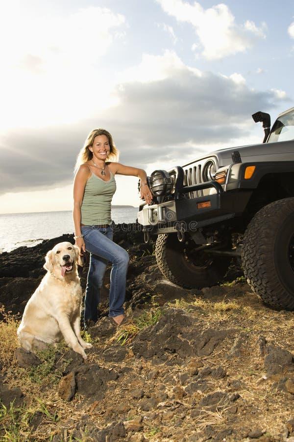 Mujer y perro por SUV en la playa fotografía de archivo libre de regalías