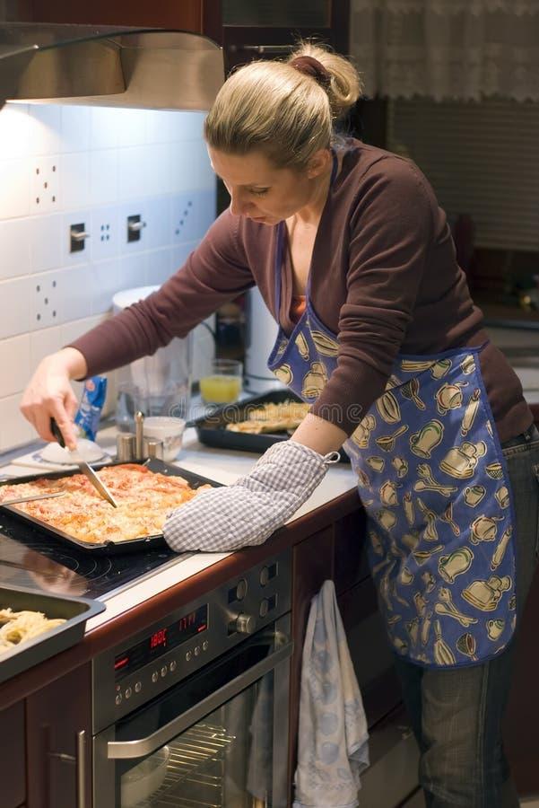 Mujer y pizza en cocina imagen de archivo